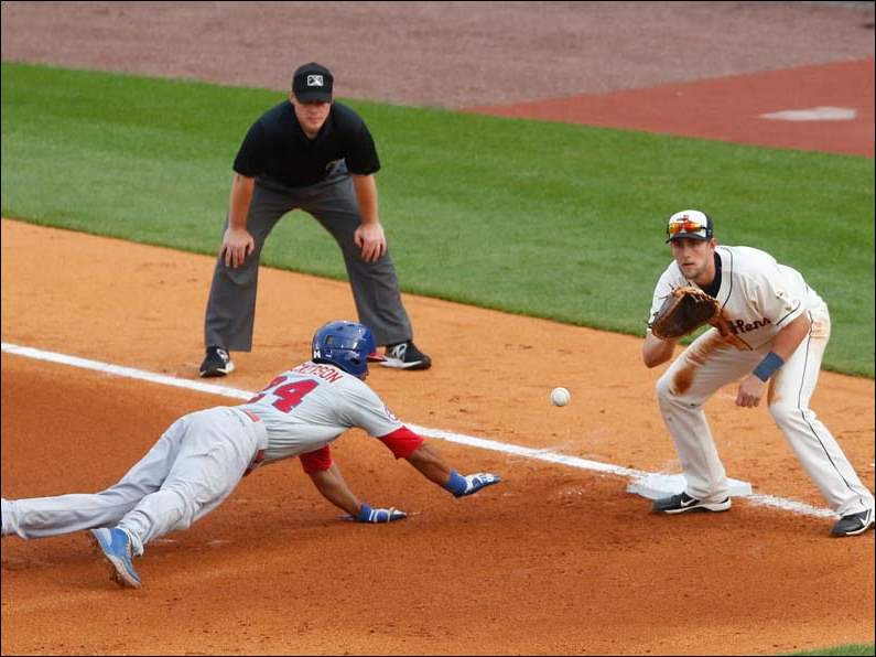 Toledo Mud Hens' Jordan Lennerton reaches to get the ball before the Buffalo Bisons' Chris Dickerson gets back to first. Dickerson was safe at first.