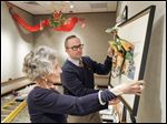 Ginny Laiho and Ben Sapp, Mazza Museum director, hang pop-up art  in the Laiho Gallery, named for Ms. Laiho, a docent, and her husband, Rikhard, who funded the expansion at the University of Findlay's Mazza Museum.