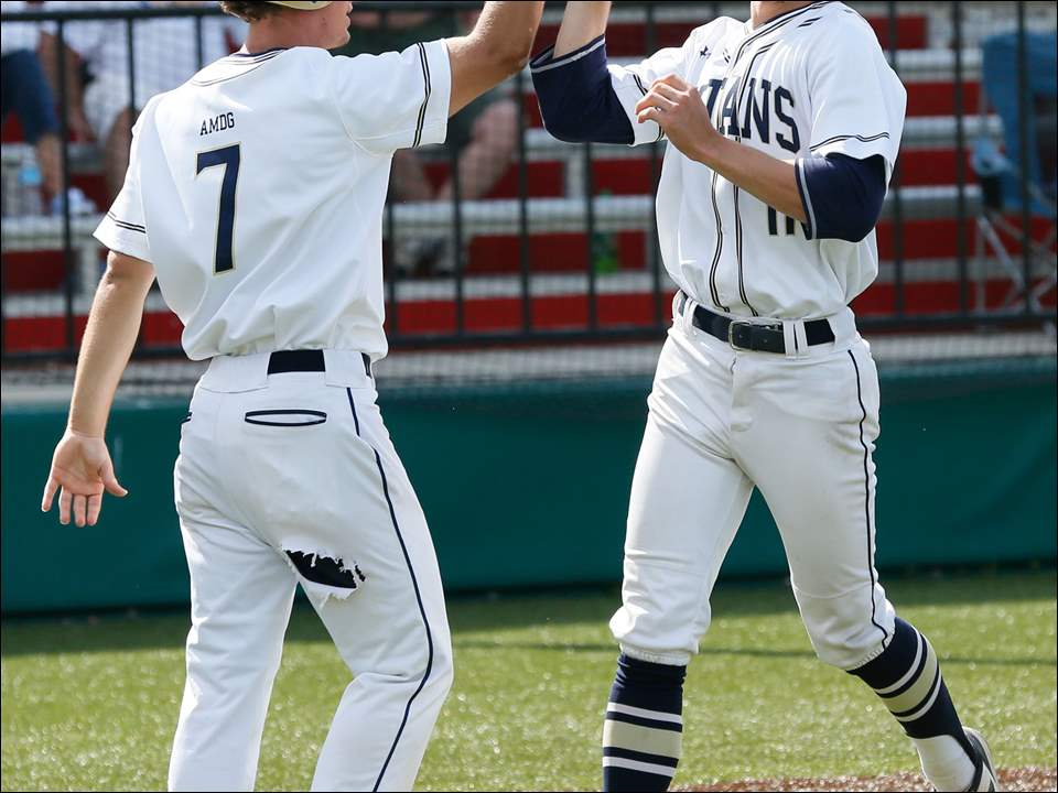 St. Johns' Jonathan Friesner (7) and TJ Lake (11) celebrate scoring against Findlay during the TRAC baseball semifinals on Monday at Mercy Field in Toledo.