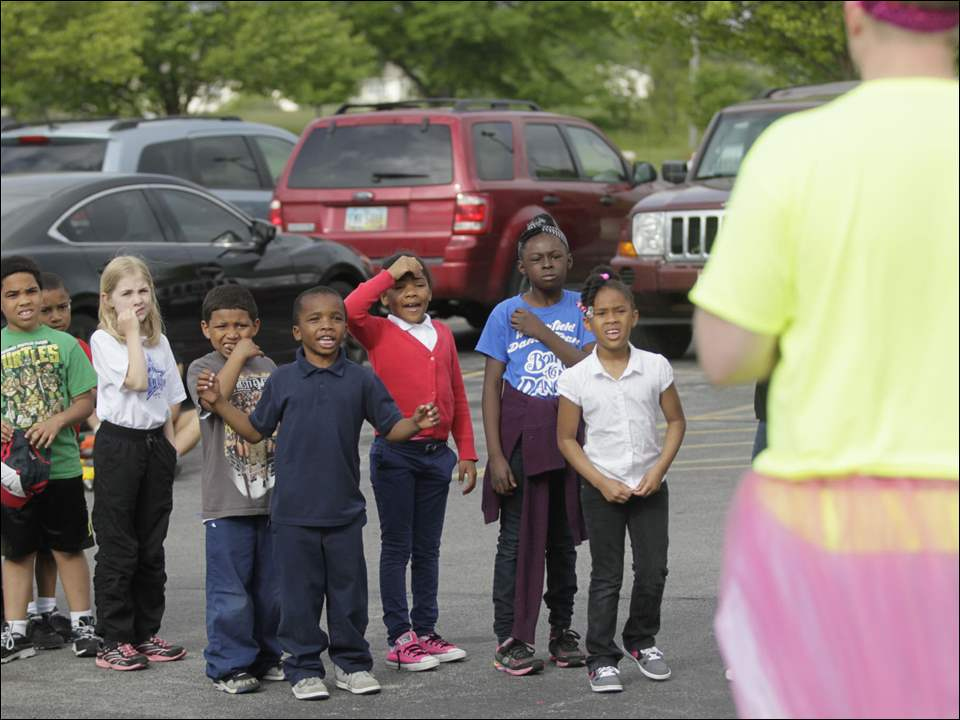 First graders in Michelle Lairson's class watch as principal Principal Nathan Preston, right,  approaches them during field day.  Nathan Preston, principal of Winterfield Venture Academy, at the Toledo, Ohio school on Tuesday. Preston, in the pink tutu, is fulfilling his promise to wear it if the school family reached its goal of donating 17 pints of blood in a recently-completed America Red Cross blood drive.