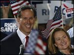 Former U.S. Sen. Rick Santorum, left, stands with his wife Karen Santorum as he announces his candidacy for the Republican nomination.