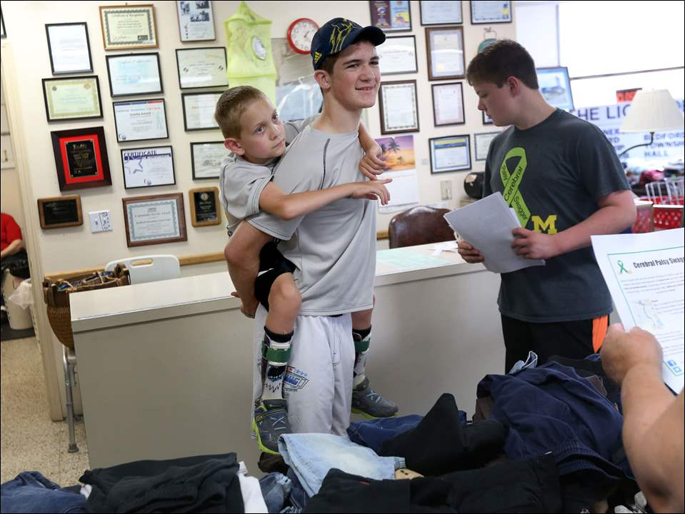 "Braden, 8, left, holds on to his brother Hunter Gandee, 15, center, as Hunters distributes fliers with the help of their friend Cole Fornwald, 15, right, at a business in Temperance on Saturday. The brothers were distributing fliers in advance of their 57-mile-long walk to Ann Arbor, which will take place from Friday, June 11 through Sunday, June 7. Hunter will carry Braden, who has Cerebral Palsy, for the duration of the walk to raise awareness of the condition and promote, ""a truly accessibly world."""