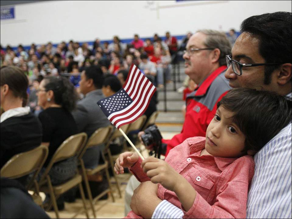Haider Siddiqui, 4, of Oregon is held by his father Vajeeh. Haider's mother, Farwa, formerly of Pakistan, was becoming a new citizen.