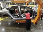 Aassembly line workers build a 2015 Chrysler 200 automobile at the Sterling Heights Assembly Plant in Sterling Heights, Mich.