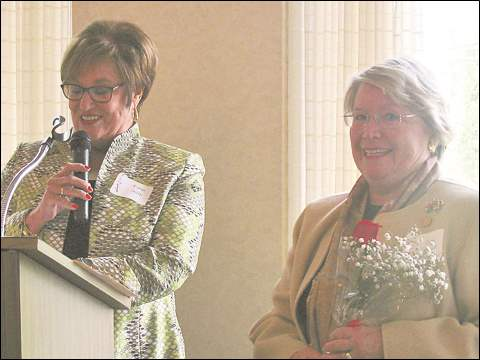 Emcee Karen Smith, left, recognizes Carol Koury for 20 years of service to Christ Child Society at the May 21 luncheon at Sylvania Country Club.
