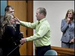 Jordan Byelich, center, husband of killed bicyclist Jill Byelich, reaches to hug Mitzi Nelson, left, in court in as her family looks on before she is taken to jail Wednesday, June 3, 2015 in St. Johns. Mich.   Nelson accused of being distracted by her cellphone when her car struck and killed Jill Byelich,  has been barred from using any portable communication device for two years. She will spend at least 90 days in jail over staggered periods and must speak to new drivers about the dangers of distracted driving.  (Rod Sanford /Lansing State Journal via AP)  NO SALES
