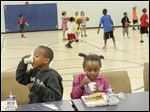 Jeremy Dixon, 6, left, and Je'myah Doss, 5, finish their lunches as other children play basketball  after a meal provided by the Feed Lucas County Children at the Frederick Douglass Center in West Toledo. The program, which got under way Monday, provides lunch during summer months for Lucas County residents 18 years old and younger.