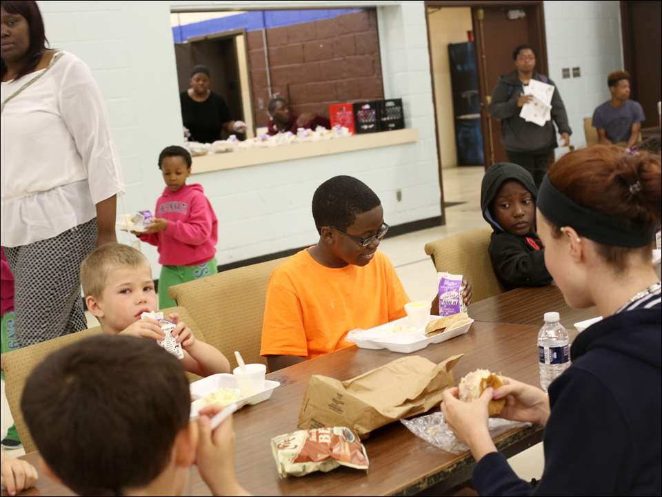 Brentten Witcher, 10, center, smiles as he reads his milk box during lunch on Monday with Feed Lucas County Children at the Frederick Douglass Center in West Toledo. The program provides lunch during summer months for any Lucas County resident 18 years old and younger.