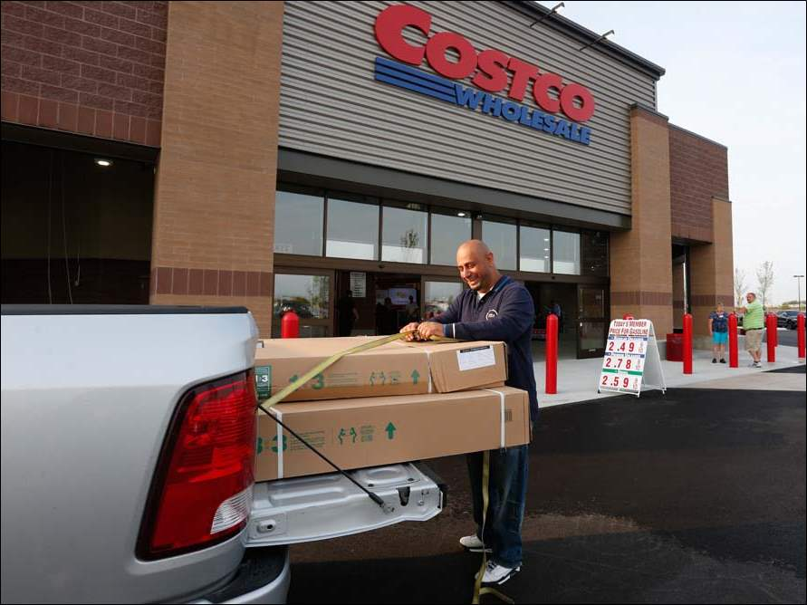 Ahmed Haidar of Dearborn, Mich., ties down a gazebo set he purchased at Costco on the morning of its opening. He came to this store because the item was sold out at the store in Michigan.