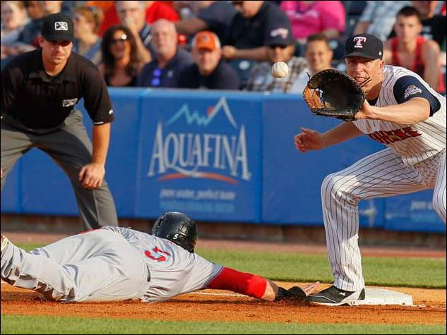 Syracuse Chiefs left fielder Jason Martinson (5) dives safely back to first base against Mud Hens first baseman Mike Hessman during the second inning.