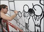 Artist Maura Amato paints a mural to honor Toledo artist Judy Dilloway, who died in 2007, on the side of a building at Adams and 11th streets in Toledo's Uptown District.