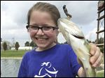 Sophia I. Rodriguez shows off a fish she caught last year at Bass Pro Shops in Rossford. The store will host its 'Gone Fishing' event Saturday and Sunday and June 20 and 21.