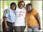 Consulea Reece, center, with Officer Flo Wormely, left, and her mother Vonnie Gaines on June 4 at the Ottawa Park Substation in Toledo. Consulea Reece just got her high school diploma. She was mentored by Officer Wormely after she entered the Toledo Police Department's STRIVE program.
