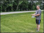 Lori Boyd and her husband, Thomas, demonstrate with a tape measure outside their home on Fort Meigs Road. The measurement, at 25 feet, is too much for them to lose, the couple say. Although many residents say that the road does need improvements, they point to the west side, where the area is mostly farmland with a ditch along it.