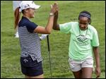 Professional golfer Lydia Ko, left, and Sha' Nya (cq) Jones, 12,  high-five during a children's golf clinic at Highland Meadows on Monday.