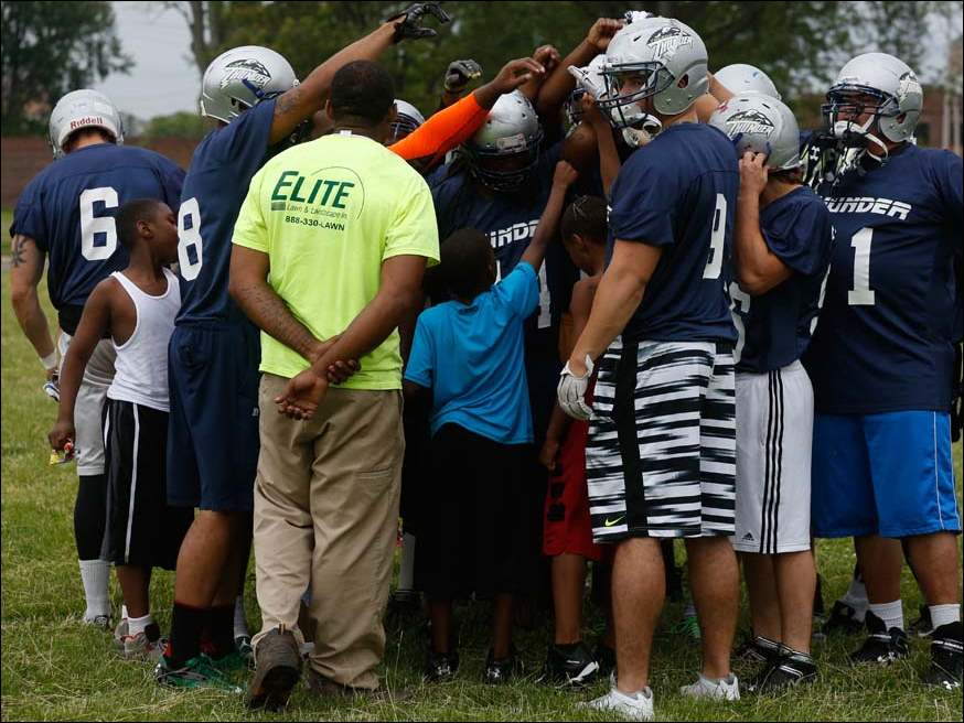 Youth football coaches and players mix with the Toledo Thunder during practice at Warren Park.