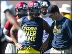 Michigan football coach Jim Harbaugh talks to Prattville's Kingston Davis during the Coach Jim Harbaugh's Elite Summer Football Camp on June 5 at Prattville High School in Prattville, Ala.