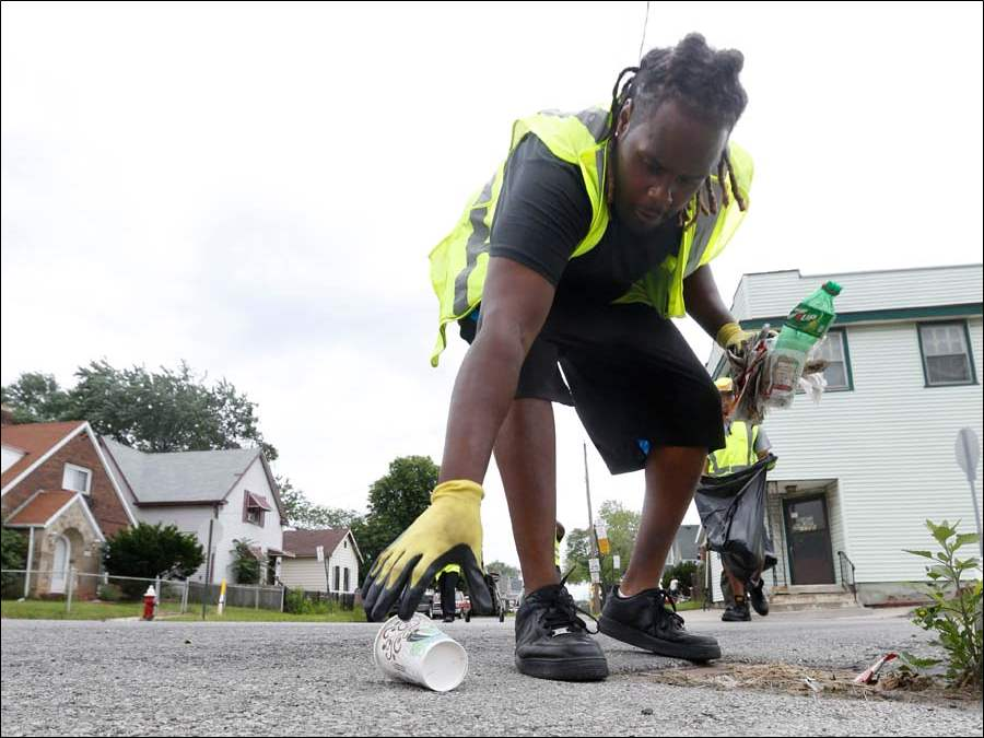 William Moore picks up a coffee cup on Buckingham Street as part of the Lucas County Summer Youth Employment Program's Green Team.