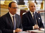 French President Francois Hollande, left, and French Foreign Minister Laurent Fabius chair a meeting at the Elysee Palace in Paris, France, today.