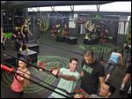 Gym instructor Javier 'Coach Java' Martinez, second from right, guides participants doing inverted rows on a jungle gym at the Fhitting Room boutique fitness studio in New York.