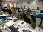 Spc. Yahshem Hicks, right, and Spc. Anthony Young take part in a computer training class at Fort Hood, Texas. The men are participants in Shifting Gears, a program sponsored by General Motors that teaches automotive skills and tries to match participants with dealerships around the country.