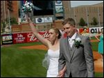 Bride Rachel Burgess raises her bouquet as she and her new husband, Ryan Anderson, leave home plate after being married May 30 at Fifth Third Field.