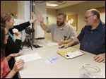 Katelynn LaPrad, a vital records clerk, gives Robert Campbell a high five as he and Jeffrey Town, right, apply for a marriage license in Monroe. At far left is Laura Keehn, a vital records supervisor.
