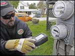 Mark Delbeck of Burlington Electric checks a 'smart reader' in Burlington, Vt. The study of 30,000 low-income houses in Michigan found that projected savings were 2.5 times greater than actual savings.