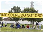 Protesters along Preserve Promenade Park have a picnic inside a 31,200-square-foot area they outlined with Crime Scene tape Sunday. The area is slated to be a parking garage.