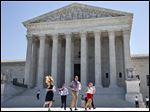 New interns run with a decision across the plaza of the Supreme Court in Washington, today.