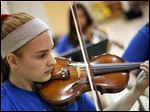 Hannah Asselin plays her violin during a rehearsal of Greater Toledo International Youth Orchestra.