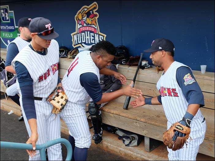 Mud Hens pitcher Angel Nesbitt slaps five to second baseman Alexi Casilla before playing the Durham Bulls Tuesday. Casilla was traded from Durham to Toledo on Monday.