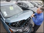 Mike Johnson, a sales manager at a Honda car dealership, opens the hood of a Honda CRV SUV, in Tempe, Ariz.