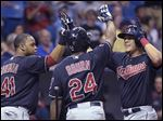Cleveland Indians' Giovanny Urshela, right, is congratulated by Carlos Santana (41) and Michael Bourn (24) at home plate after hitting a three-run home run.