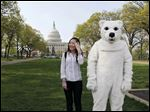 Yuan Yuan Deng, left, visiting from Long Island, N.Y., poses for a souvenir snapshot beside environmental activist Brian McLeane of the Alaska Wilderness League, dressed in a polar bear suit as he waits to participate in a protest on Capitol Hill in Washington in April, 2011.