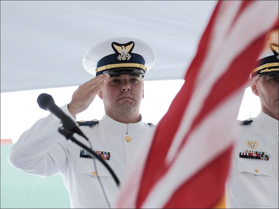 Lieutentant Commander Anthony Migliorini, left, and Commander Charles Bright, right, salute the flag.