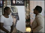 Sophia Lewis, left, with PSEG Long Island, speaks to an attendee about employment opportunities during a job fair at Citi Field in New York on Tuesday.