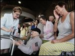 Horace Appleby, a 101-year-old veteran, is presented a Silver Star and Bronze Star from U.S. Rep. Marcy Kaptur, as his great-niece Renee Hahn, Perrysburg, wipes away a tear at One Maritime Plaza in Toledo on Thursday.
