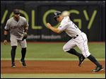 Tampa Bay Rays' Grady Sizemore takes off on the pitch to steal second base as Cleveland Indians' Carlos Santana, left, looks on.