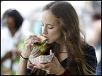 Angie Shinozaki of Troy, Mich., takes a bite of a burger during the  Burger Bash and Dash of Northwest Ohio. Proceeds from the event, held as part of Red, White, KABOOM, will benefit St. Paul's Community Center.