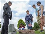 The Bleau family, from left,  John, Jadyn, Jaci, Landon, and Kennedy gather around the grave of World War II veteran Pfc. Forrest B. Stubbs' grave at Willow Cemetery in Oregon.