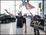 Former Toledo Mayor Carty Finkbeiner and volunteers Adel Kamal, right, and Dave Anderson, back, wave to motorists at the Wernerts Corners intersection of Laskey, Douglas, and Tremainsville roads. Mr. Finkbeiner stands at busy intersections to display his signs.