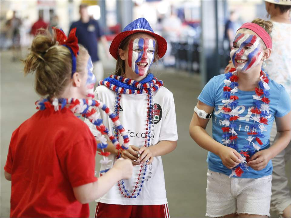 U.S. Women's National Team fans Elle Hurst, left, 11, of Toledo, Gayle Rudolph, center, 11, from Perrysburg, and Livia Hurst, 11, of Toledo, painted red, white and blue, on their faces during a watch party at Fifth Third Field.