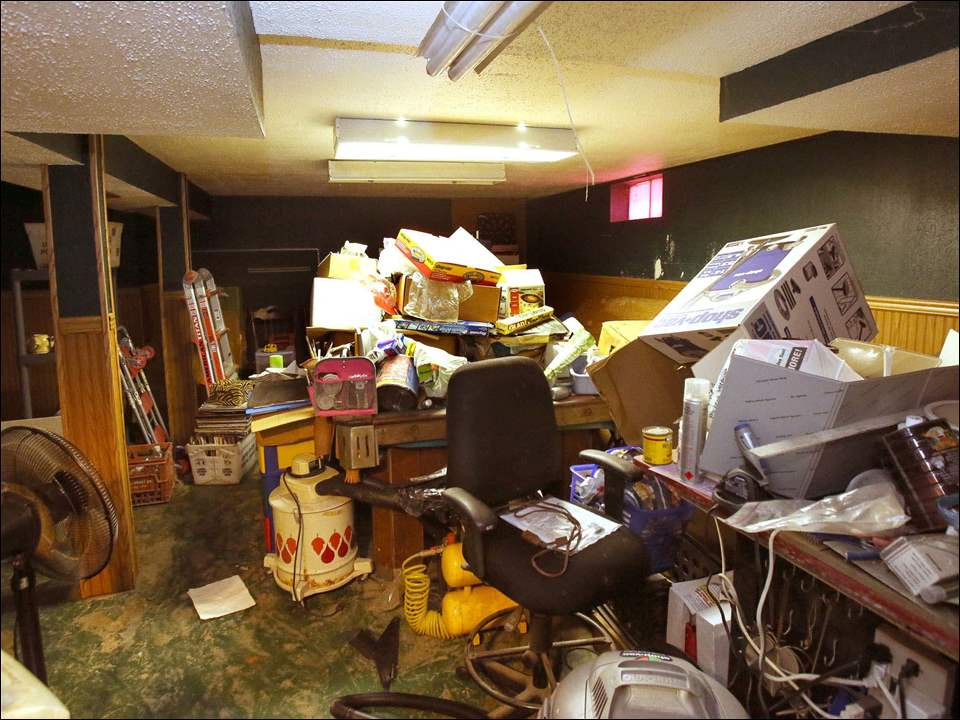 The pool table, center and behind the chair, was under water,  as were the items the Hutkas have piled on top of it to help the floor to dry. They are running fans and air conditioning in the basement.