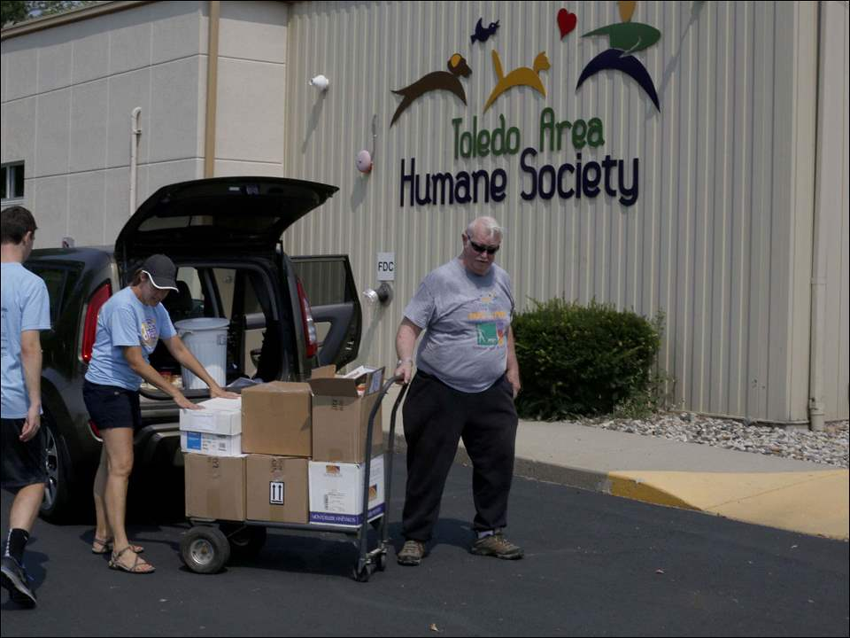 Kelle Pack, director of development for the Toledo Area Humane Society, center, and volunteers Thomas Cunliffe, left, and Dick Heffelfinger, right, move boxes.