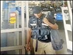 In this July 4, 2015 frame from surveillance video provided by the Bristow Police Department, a man leaves with more than $75,000 from a Wal-Mart after disguising himself as an armored truck driver in Bristow, Okla. Authorities say the suspect walked to the cash office, signed for the deposit and walked out of the store. (Bristow Police Department via AP)
