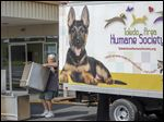 Jim Britts, who handles maintenance at the Humane Society, helps unload a moving truck on Monday in Maumee.
