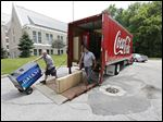 University of Toledo employees Chris Graham, left, and Bob Guerrero unload a water cooler to be placed in Horton International House as Coca-Cola products replaces Pepsi.