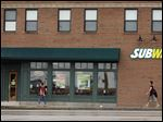 People walk past a Subway restaurant in St. Louis. The sandwich chain has faced a string of difficulties.