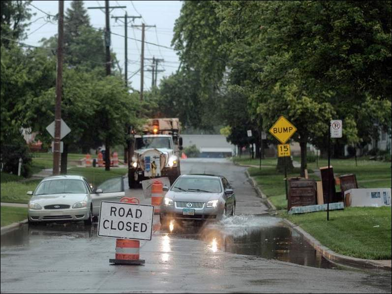 A car drives through high water on Burnham Avenue near Poinsetta as a City of Toledo truck is parked nearby as water is pumped from the street to Laskey Road, Thursday.